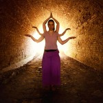 Woman with many hands representing Shiva, standing in the dark tunnel.